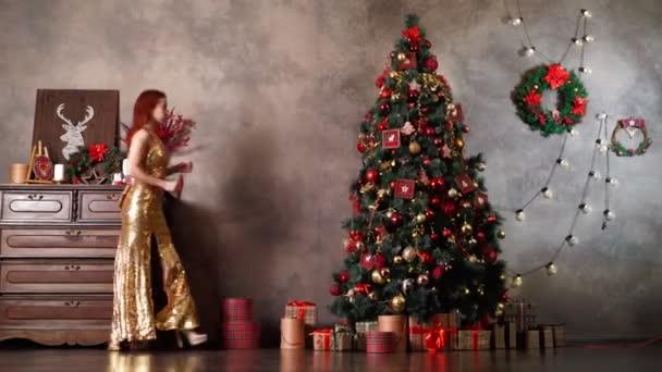 Krásná žena ve zlatých šatech zdobí vánoční stromek s novoroční hračky