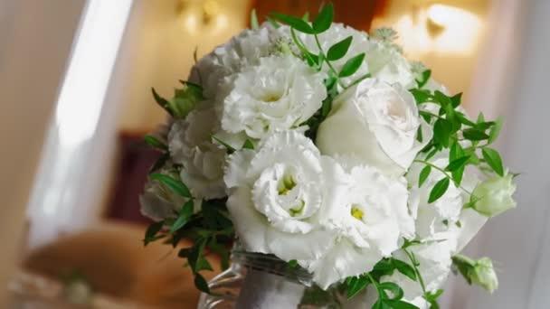 Detailní záběr. Krásná svatební kytice z bílých růží stojí na parapetu.