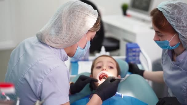 Two Woman doctors in a dental clinic, serve the patient little boy. Work Dentist
