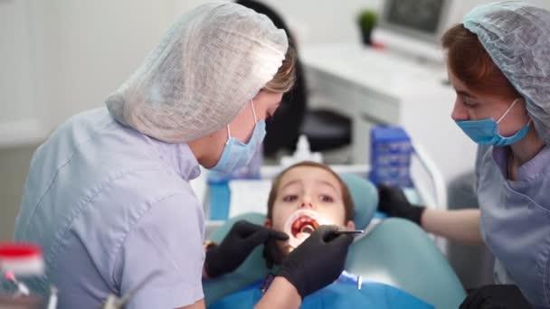 Dvě doktorky na zubařské klinice, obsluhujte trpělivého chlapečka. Pracovní zubař