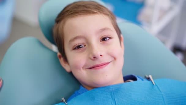 Doktor v zubní klinice mluvit s legrační malý chlapec práce zubař s dětmi