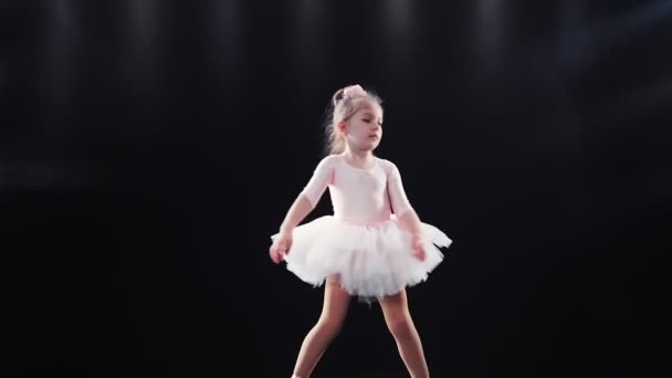 Kleine Mädchen Ballerina kaukasischen Auftritt in einem rosa Tutu tanzt auf der Bühne. Kinder. Zeitlupe.