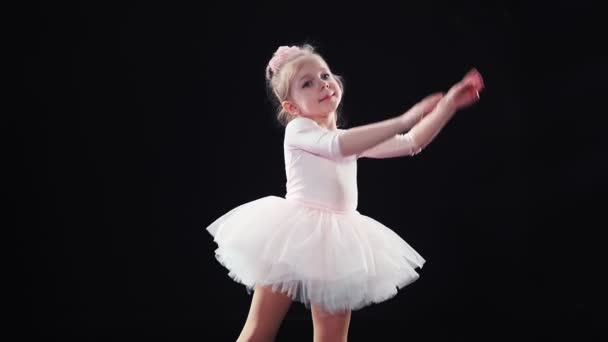 Little girl ballerina Caucasian appearance in a pink tutu dances on stage. Children. Slow motion.