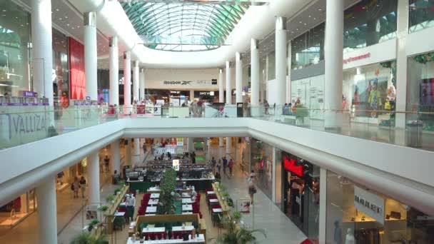 Interiér se sloupy moderního nákupního centra, obchody, kavárny a restaurace, lidé v obchodě s lékařskými maskami během epidemie koronaviru COVID-19 v sebeizolaci Kyjev, Ukrajina 13.09.2020 Ocean Plaza.