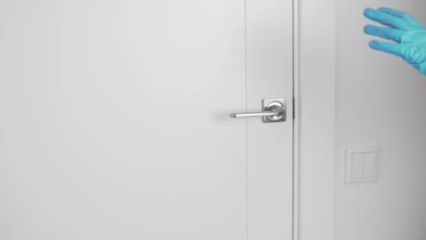 Lassú mozgás, egy női kéz egy orvosi kesztyűben kinyitja az ajtót a kilincs mögött.