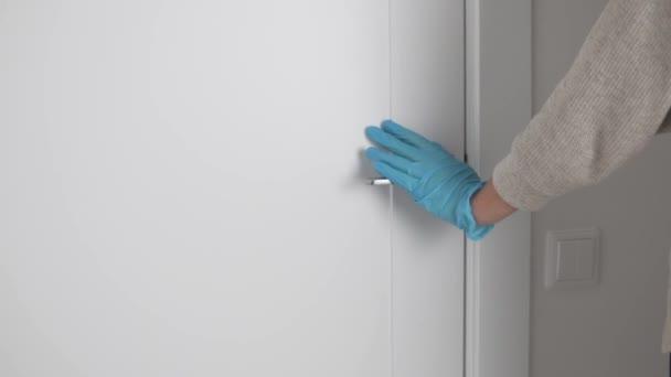 Ženská ruka v ochranné rukavici zavře dveře a rozsvítí světlo v místnosti.
