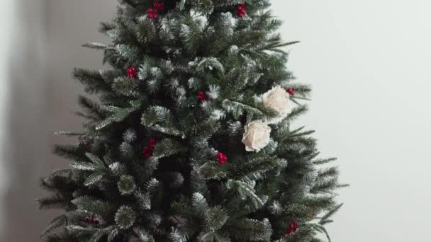 Roztomilá holčička v kostýmu Santa Clause zdobí umělý vánoční stromek s květinami na Štědrý den