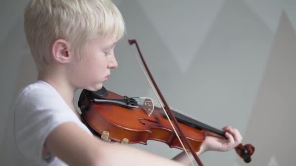 Egy gyönyörű szőke fiú hegedülni tanul egy zeneiskolában.