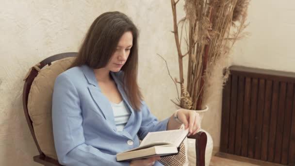 Eine Lehrerin liest in einem Stuhl ein dickes Buch