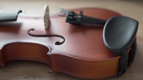 Közelkép a hegedű feléről híddal az asztalon