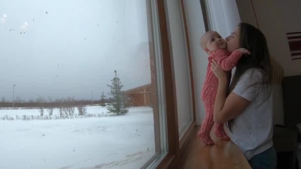 Máma jemně líbá malé dítě doma u okna v zimě