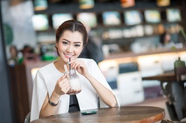 Beautiful woman drinking sweet drink in Cafe