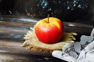 apple on a black background wooden table linen napkin
