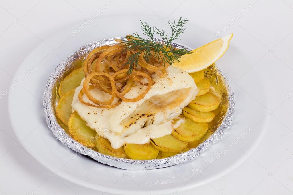 white fish with potatoes, fried onions, dill, lemon in foil on the
