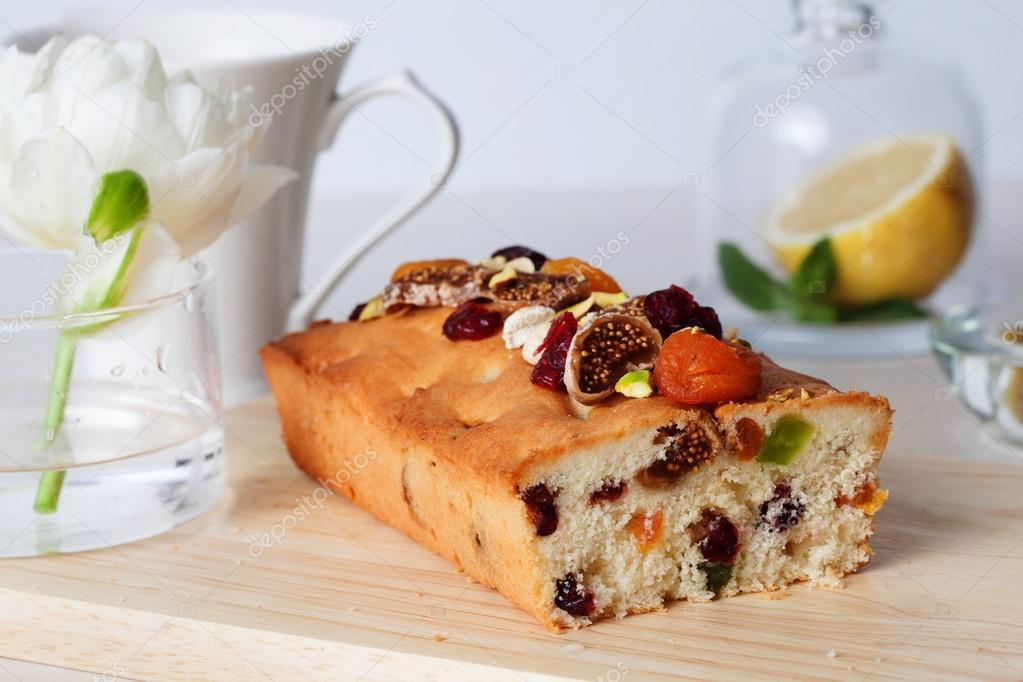 plum cake food candied fruits, nuts, dried apricots, figs, close-up still life with tea and lemon