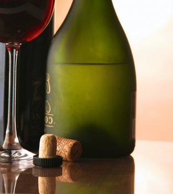Elegant wine glass and a wine bottle in dark background