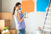 Photo Happy smiling woman painting interior wall of new house