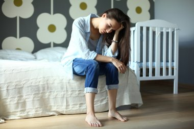 Young tired woman sitting on the bed near childrens cot.
