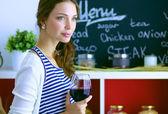 Hezká žena pije víno doma v kuchyni