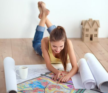 Portrait of female painter sitting on floor near wall after painting