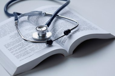a medical stethoscope on an open book