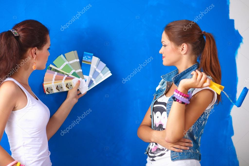 Two Young beautiful women holding color palette , standing near wall.