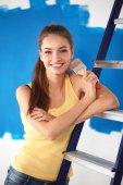 Fotografie Happy krásná mladá žena dělá nástěnné malby, sedí na žebříku