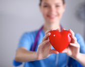 Mladá žena doktor drží červené srdce, stojící na šedém pozadí