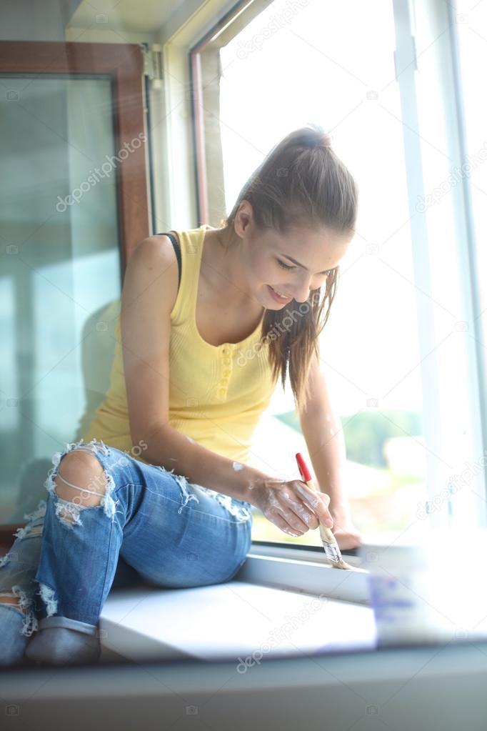 Frau Malerei Mauer einer Wohnung mit einem Pinsel sorgfältig ...