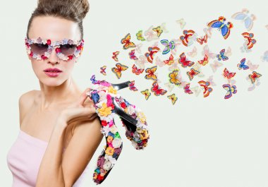Beauty woman wearing sunglasses and holding shoes