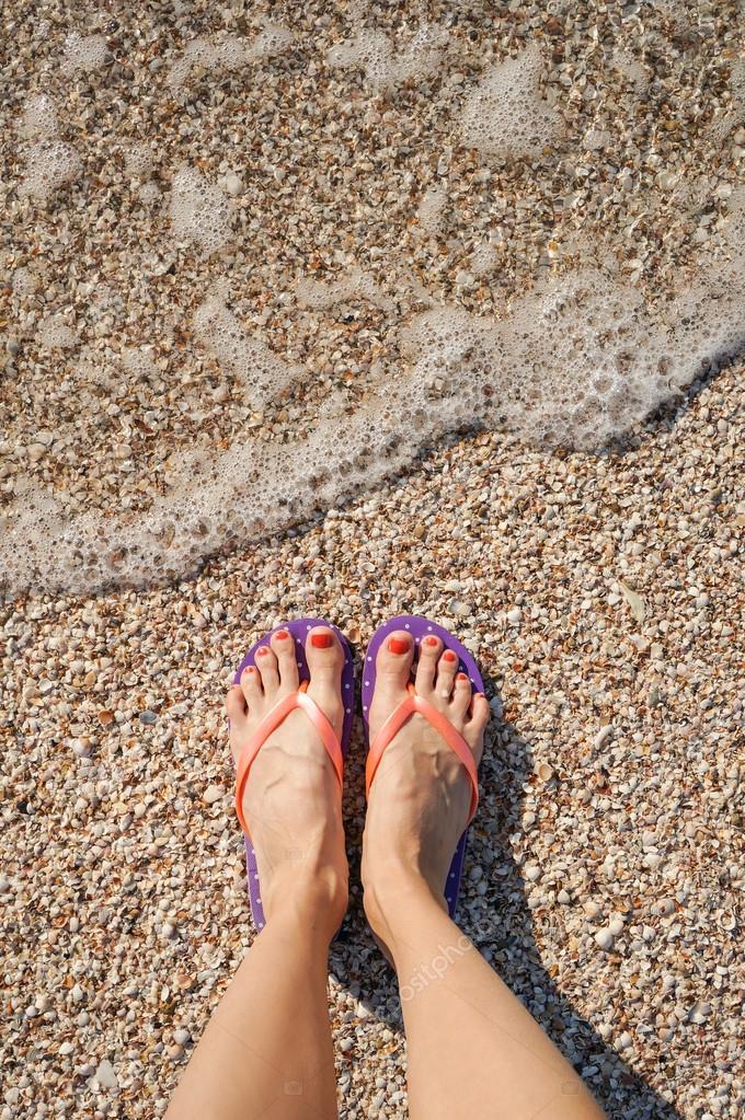 Female legs wearing flip flops near sea
