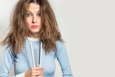 Funny woman with messy hair holding straightening irons