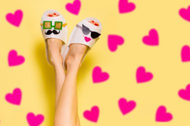 Young couple in love concept. Woman in funny slippers creative idea