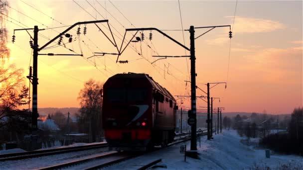 Malá lokomotiva vzdaluje fotoaparát, v zimě při západu slunce