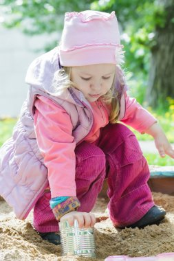 Three years old girl playing with metal tin can in playground sandbox