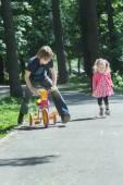 Geschwister Kinder spielen Tag-Spiel durch Laufen und Reiten Kinder Dreirad