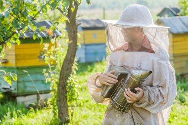 Teenage beekeeper and beehive on bee yard