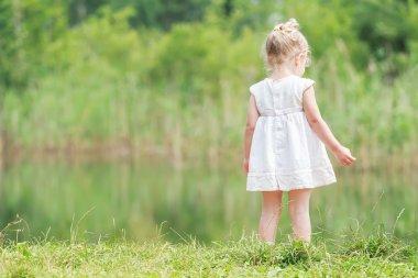 Little girl in light summer dress near forest pond