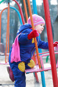 Zweijähriges Mädchen sitzt auf Spielplatz-Schaukel