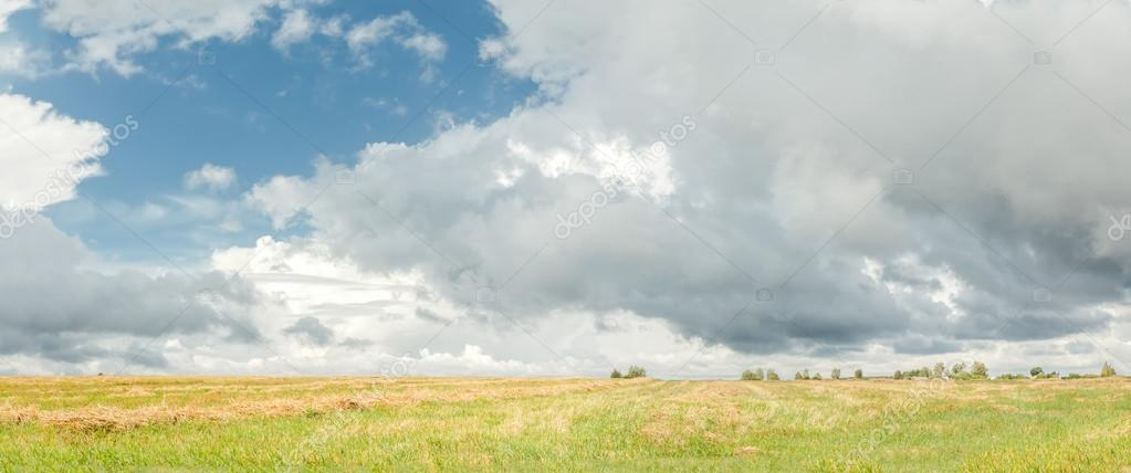 Cumulus on azure sky above harvested grain field