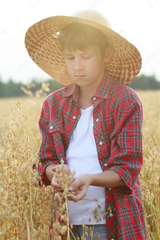 Portrait of teenage farmer boy holding oat seeds with outer shells in cupped palms with sun flare