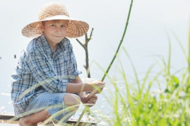 Angling teenage boy with handmade green twig fishing rod