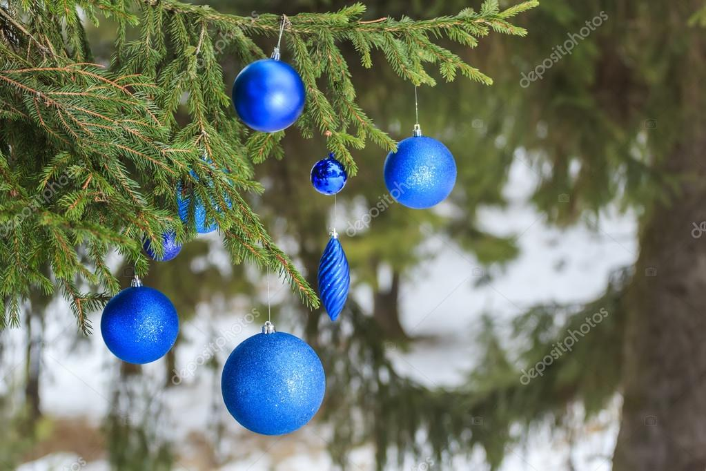 Outdoor Christmas azure shiny bauble ornaments hanging on snowy spruce twig
