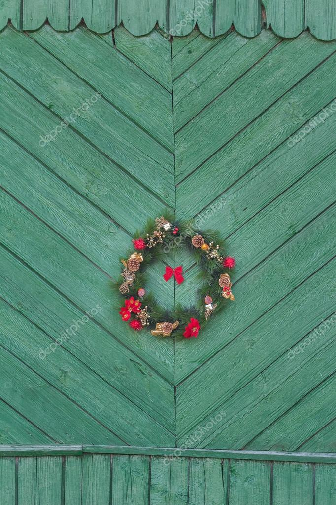 Festive X-mas outside wreath hanging on old rustic green door