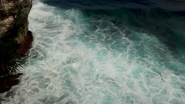 Amazing top aerial slow motion view of azure ocean and giant waves crashing at rocky cliff with splashing and white foam. Bali island, Indonesia