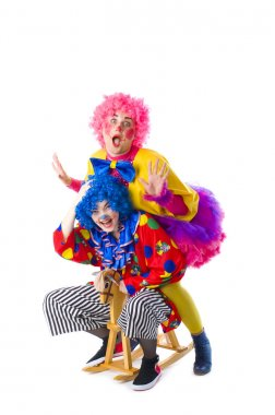 two funny colorful clown fooling around on a white background
