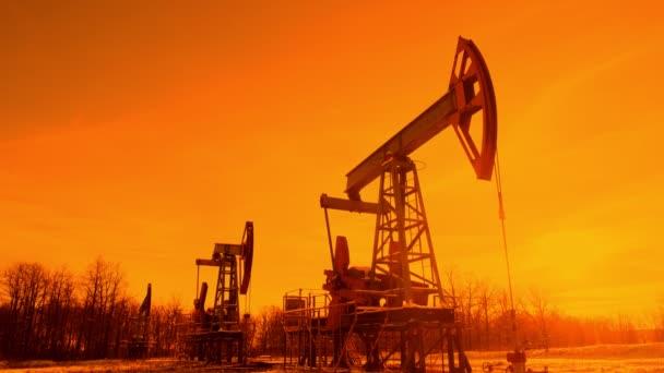 egy olajgép sziluettje. olajszivattyú a naplemente hátterében. Kiváló minőségű 4k felvételek
