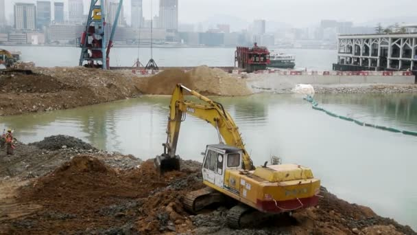 Working Excavator on filling the dam