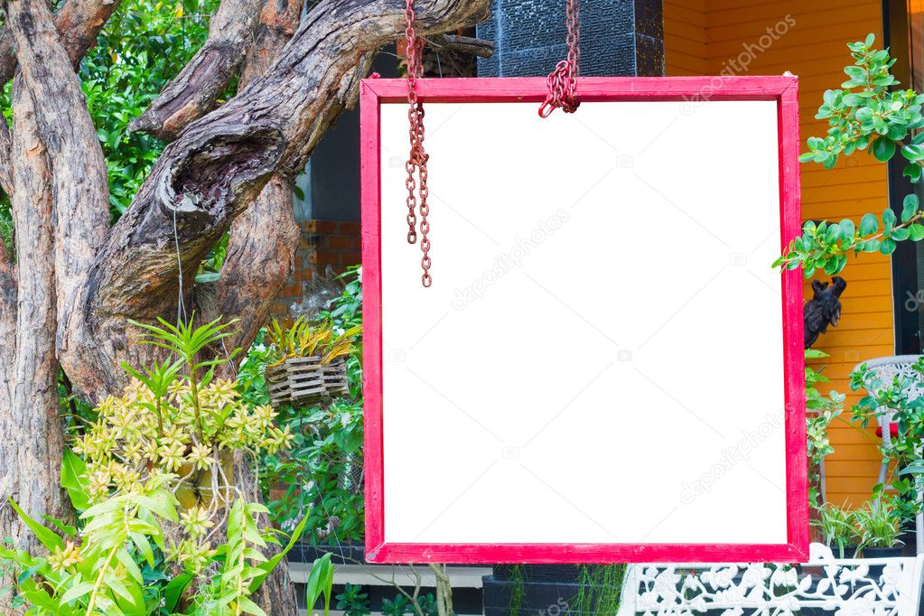 isolated red frame hung on tree in lush garden setting, clipping ...