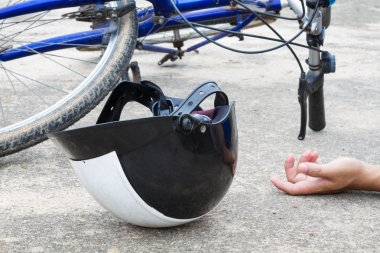 bicycle and a helmet lying on the road with hand of human, accid